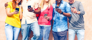 Teenagers texting mobile phone messages row on pink background -