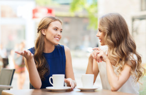 young women drinking coffee and talking at cafe